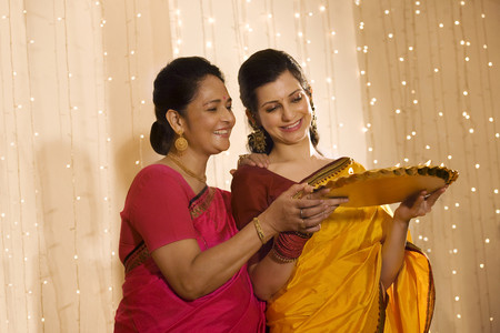 down lights: Mother and daughter with a tray of diyas Stock Photo