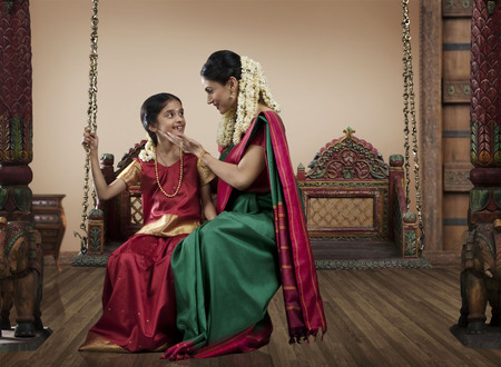 gajra: South Indian woman sitting with her daughter on a jhula