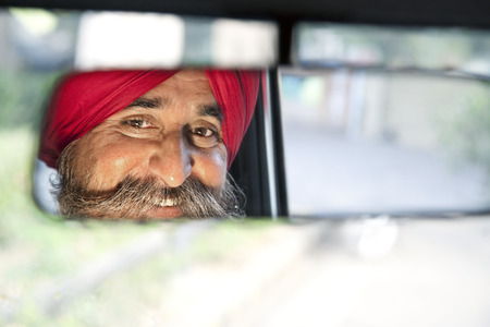 Sikh taxi driver looking into the rear view mirror Stock Photo