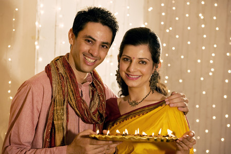 25 30: Couple holding a tray with diyas