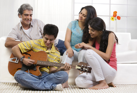 front house: Boy playing the guitar for his family