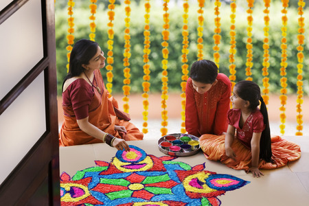 sutra: Woman making a rangoli while her children watch Stock Photo