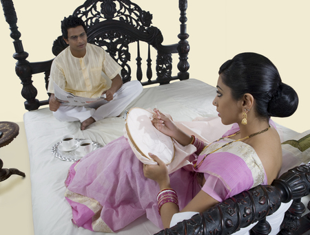 sutra: Bengali woman stitching while husband reads the newspaper