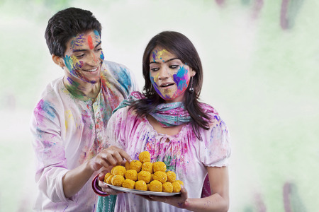 Man taking a laddoo from a tray Stock Photo