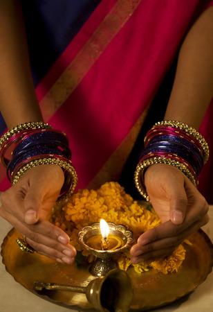 identidad cultural: Hands cupped around a diya