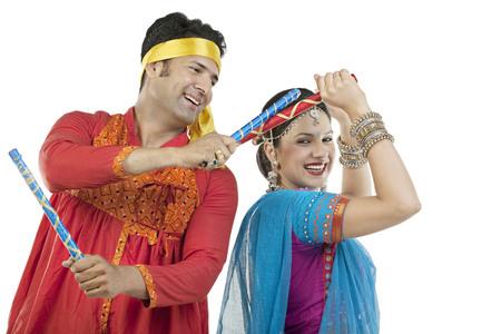 Gujarati couple performing dandiya dance