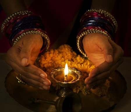 25 30: Hands cupped around a diya