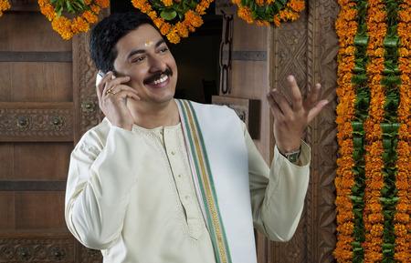 joyfulness: South Indian man talking on a mobile phone