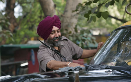 Sikh taxi driver cleaning his vehicle Stock Photo