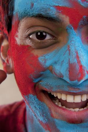 joyfulness: Mans face covered in holi colours Stock Photo