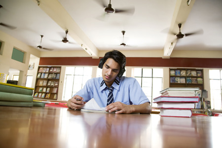 high ceiling: Boy listening to music in a library Stock Photo