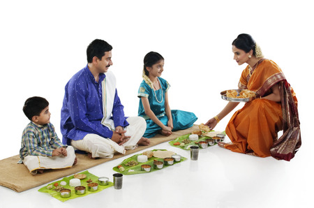 South Indian woman serving food to her family Stock Photo