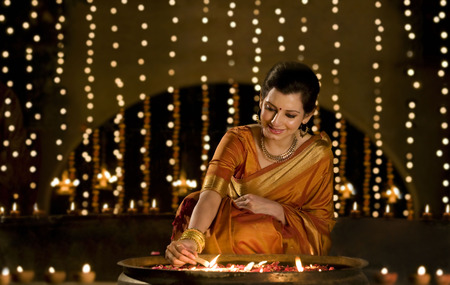 down lights: Woman lighting diyas Stock Photo