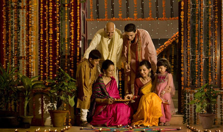 indian happy family: Family arranging diyas