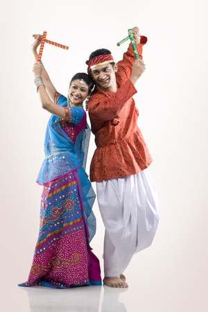 Gujarati couple performing dandiya
