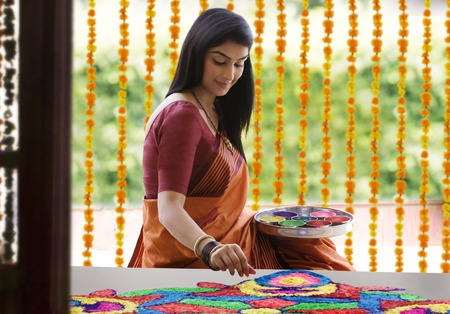 sutra: Woman making a rangoli