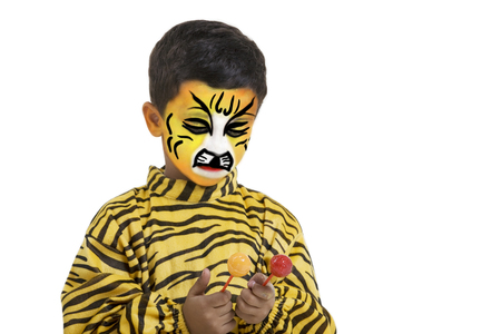 Boy in a tiger costume holding two lollipops Stock Photo