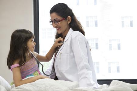 pretending: Girl checking a doctors heartbeat