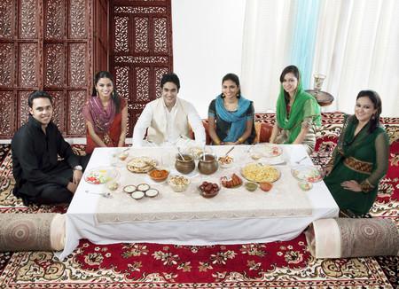 religious clothing: Muslim people having food during Id