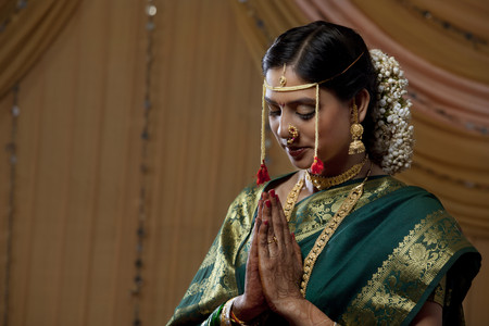 gajra: Beautiful young bride praying with eyes closed