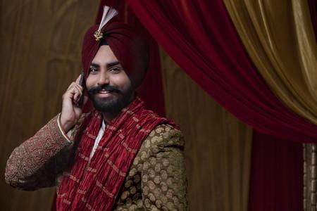 kurta: Portrait of groom having conversation on mobile phone Stock Photo