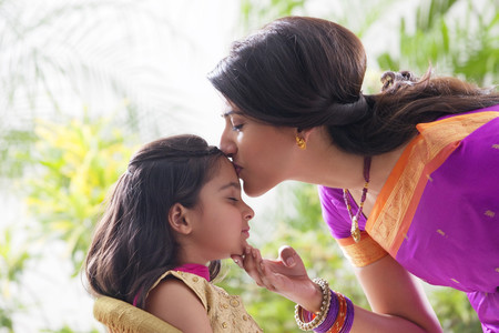 hand on forehead: Woman kissing her daughters forehead Stock Photo