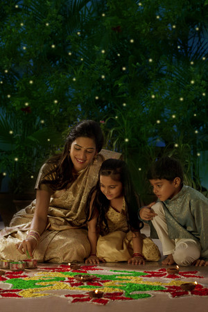 down lights: Woman making a rangoli with her kids Stock Photo