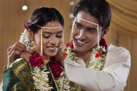 nose ring: Smiling groom performing rituals with his bride Stock Photo