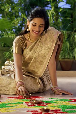 source of light: Woman arranging diyas