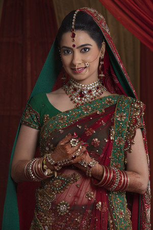 ring stand: Portrait of beautiful young bride in traditional outfit