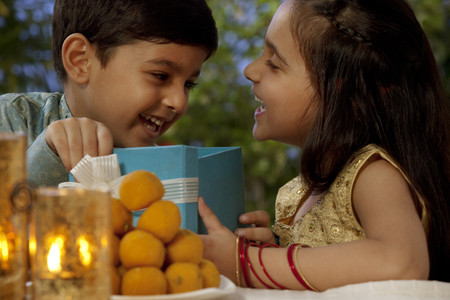 open source: Boy and girl opening gifts on Diwali