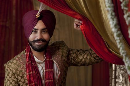kurta: Close-up of groom wearing traditional Sikh wedding costume