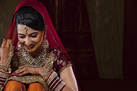 nose ring: An attractive bride looking down and smiling