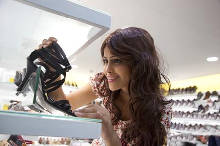 admiring: Woman admiring a shoe in a mall