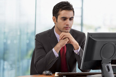 welldressed: Businessman looking at monitor screen in office