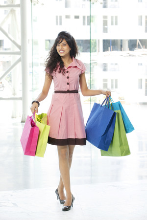 only 1 woman: Full length of young woman smiling while holding shopping bags Stock Photo