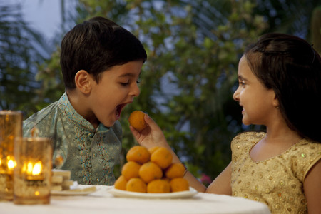 open source: Girl feeding her brother a laddoo