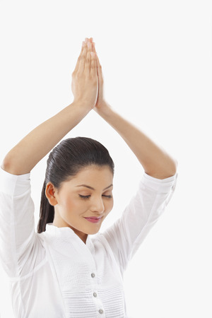 Woman practicing yoga with arms raised