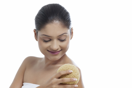 woman in bath: Close-up of smiling young woman using massage sponge Stock Photo