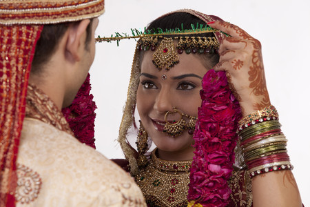 Gujarati bride putting a garland on a groom