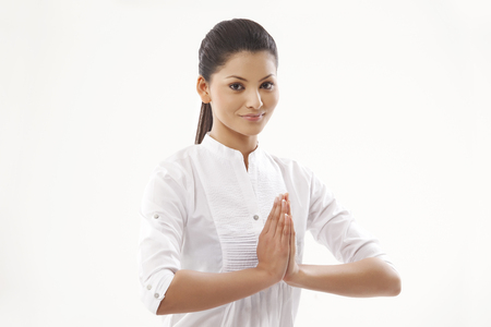 Portrait of smiling young woman with hands clasped over white background Stock Photo