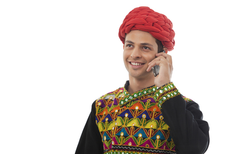 Male dandiya dancer talking on a mobile phone