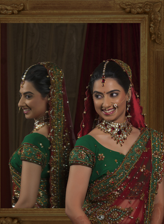nose ring: Smiling young bride standing with mirror in the background