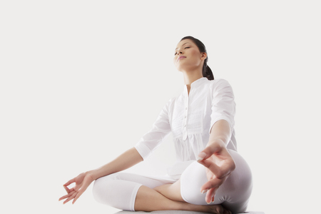 Low angle view of young woman sitting in lotus position