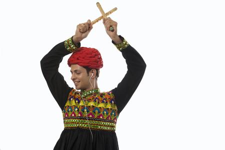 'eyes shut: Male dandiya dancer listening to music and dancing Stock Photo