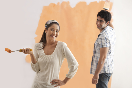 roller: Portrait of beautiful woman smiling with man painting wall in background