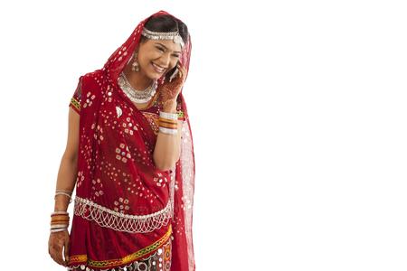Female dandiya dancer talking on a mobile phone
