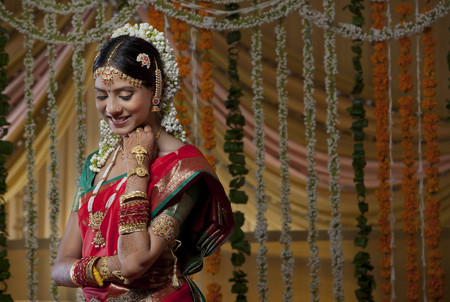 gajra: Shy Indian bride looking down and smiling Stock Photo
