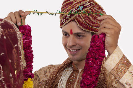 Gujarati groom putting a garland on a bride
