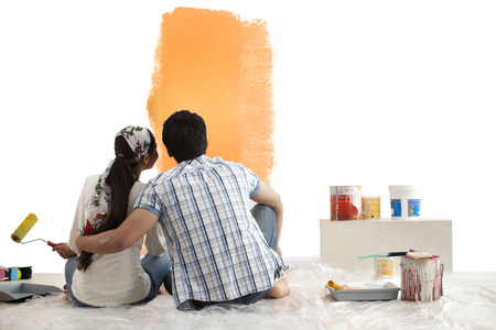 indian paint brush: Loving young couple looking at sample paint together on wall Stock Photo